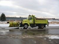 A yellow work truck with a snow plow on the front.